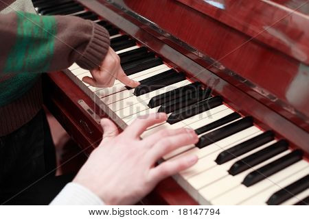 hands of a father and son playing on brown piano, black and white keys