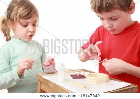 kleine Mädchen und jungen im roten T-shirt-Handwerk am kleinen Tisch, Mädchen reden