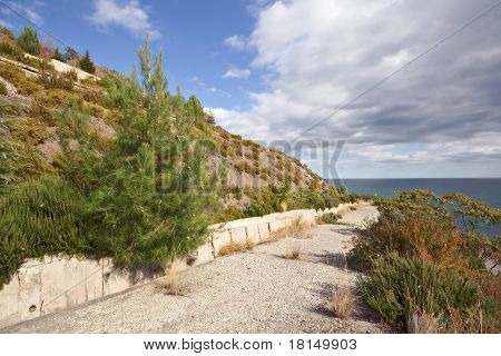 Road to Black sea in Crimea mountains among trees, grass, bushes against the blue sky with clouds. C