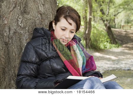 Girl Reading Book by a Tree