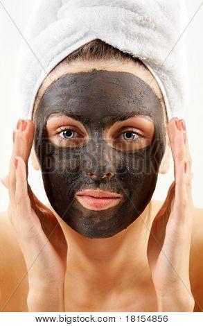 Beautiful woman with purifying facial mask looking at camera