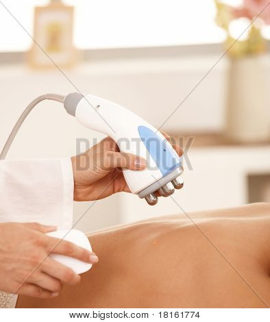 Closeup of masseur using radio frequency fat reduction equipment.?