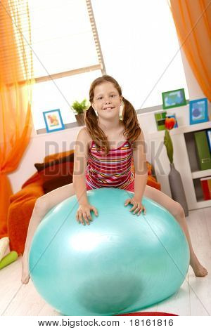 Young girl sitting on gym ball in living room, looking at camera, smiling.?
