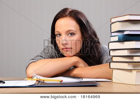 Tired From Homework Woman Rests Chin On Desk