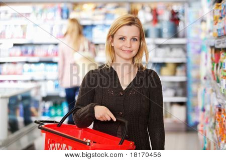 Portrait of a young woman carrying basket while shopping in the supermarket