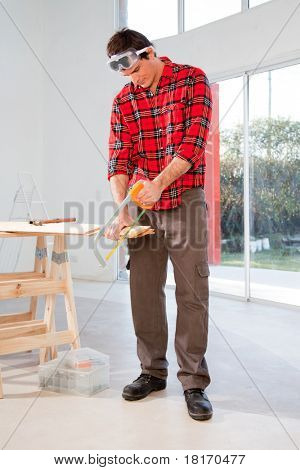 A carpenter cutting wood with a hand saw in a house