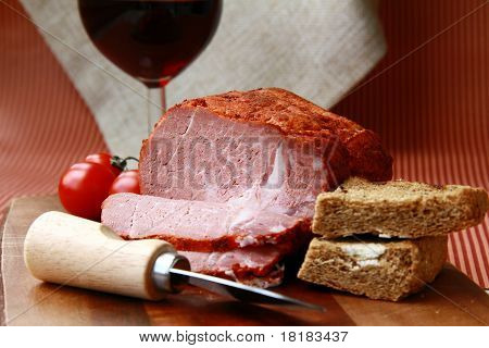 large piece of ham in pepper with a glass of red wine