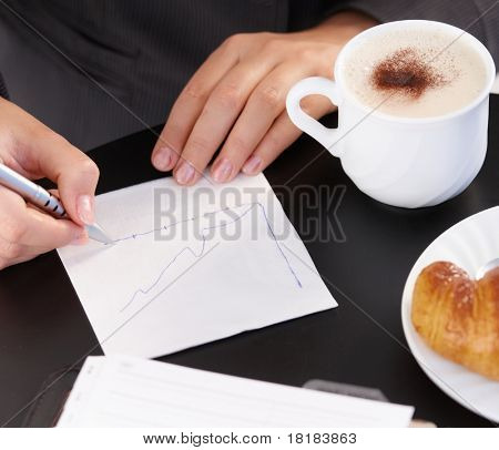 Working, drawing diagram, having coffee and croissant.?