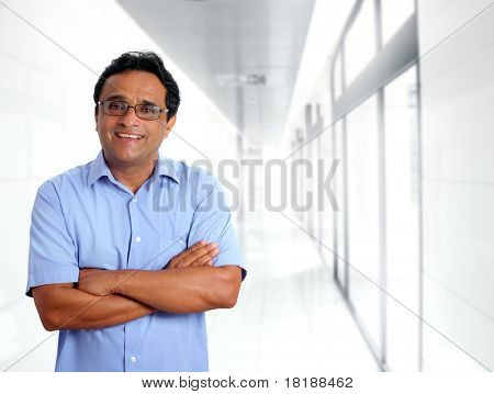 indian latin businessman glasses blue shirt in modern office corridor