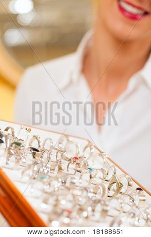Shop assistant at the jeweler with jewellery