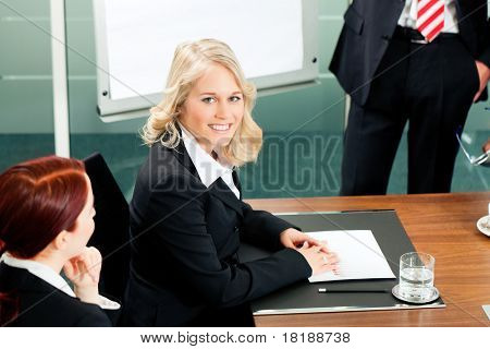 Business - presentation within a team meeting; a colleague is standing on the flipchart