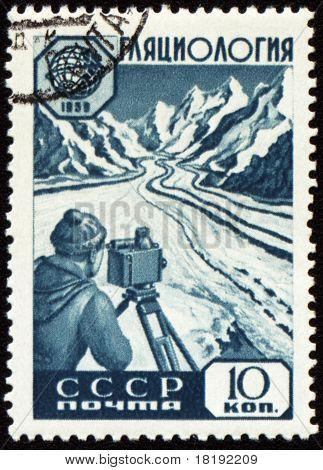 Investigador con dispositivo en montaña en sello de correos