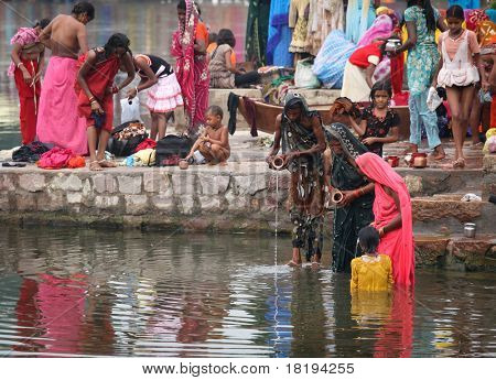 KHAJURAHO, INDIA - NOVEMBER 8: Unidentified Hindu people wash themselves in the holy ritual of daily washing on November 8, 2010 in Khajurao, India,
