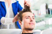 Female coiffeur washing men hair in hairdresser shop poster