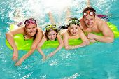 stock photo of swimming pool family  - Cheerful family in swimming pool smiling at camera - JPG