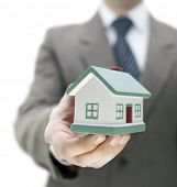 picture of real-estate agent  - Real estate agent holding a toy house - JPG