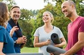 Happy multiethnic group of mature people holding yoga mat and towel in conversation after exercising poster