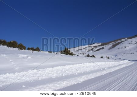 Tracks On Snow Covered Road In Mountain