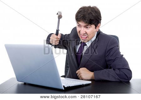 young crazy business man with a hammer smashing a laptop