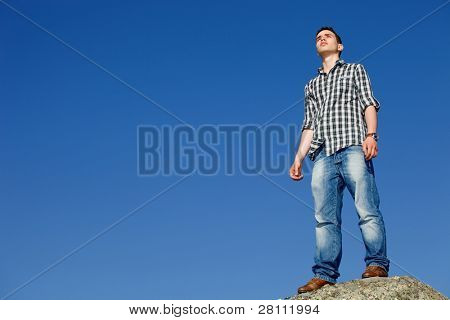 young casual man on top of a rock with the sky as background