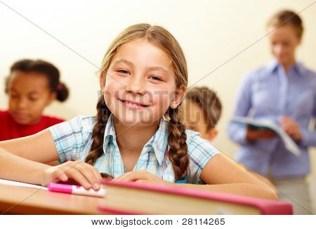 Portrait of lovely girl looking at camera with smile in classroom