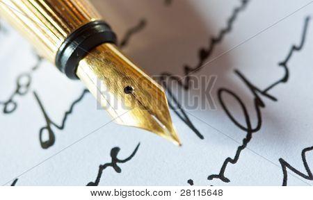 Gold fountain pen on hand written letter