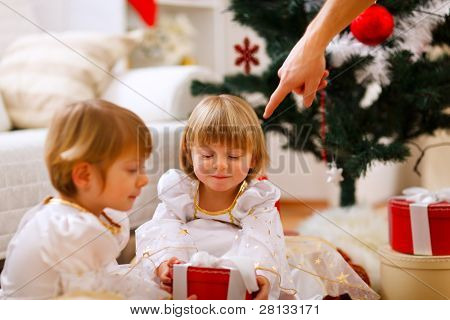 Hand Of Parent Pointing On Present To Twins Girl
