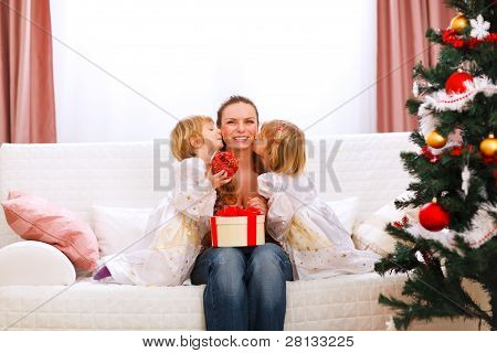 Two Twins Daughters Presenting Gift To Mother And Kissing Her Near Christmas Tree
