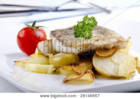 Haddock Fillet On A Plate With Grilled Potato And Garlic