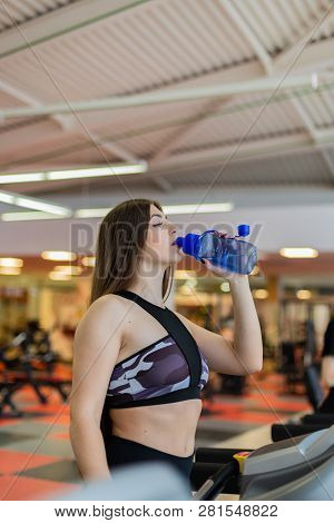 poster of Gym Woman Working Out Drinking Water Smiling Happy Standing By Moonwalker Fitness Machines. Beautifu