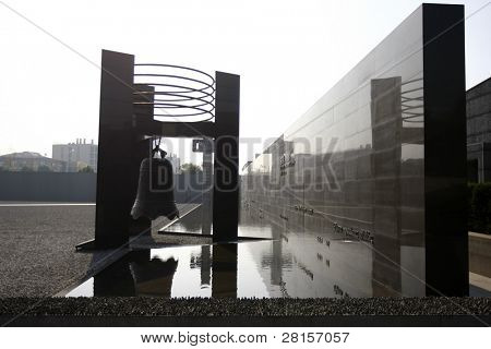 NANJING, CHINA - NOVEMBER 24: An ancient bell adorns the exterior wall of the Massacre Memorial Hall remembering the 300,000 killed, awaits visitors to this landmark on Nov 24, 2011 in Nanjing, China.