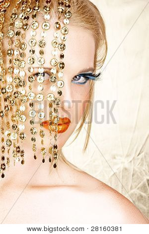 Close-up portrait of a sensual beautiful blond woman model face with bright fashion make-up, orange lips and long eyelashes hiding behind gold accessories