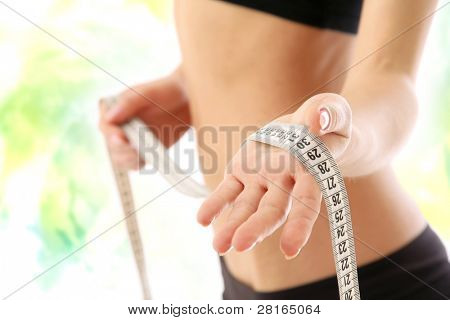 A woman measuring her waist, focus on her hand, isolated on white