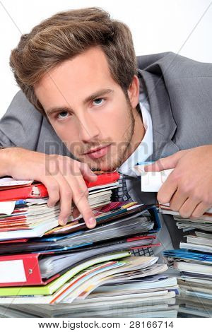 young man lying down on a desk full of binders and notebooks