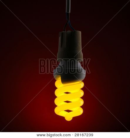 A lit energy saving light bulb on red background