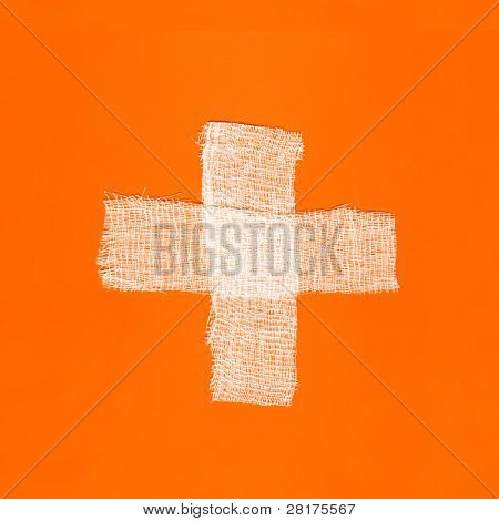 Two white bandages forming a cross on orange background