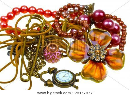 Abstract composition of vintage embelishments: string of beads, chain, pendant, watch  isolated on white background