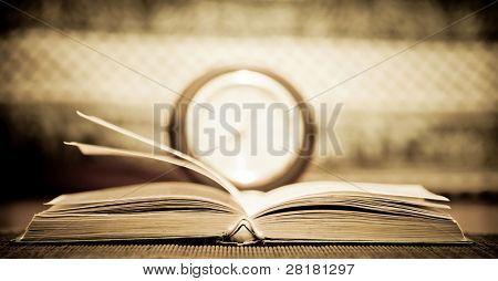 Öffnen Sie alte Buch und verschwommen Uhr im Hintergrund