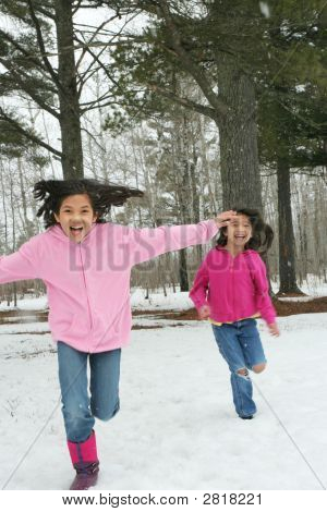 Two Girls Running Through The Snow