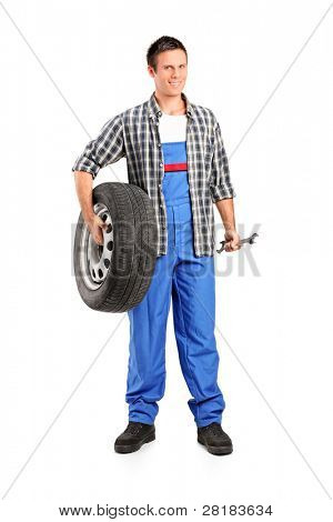 Full length portrait of a mechanic holding a spare tire and holding a wrench isolated on white background
