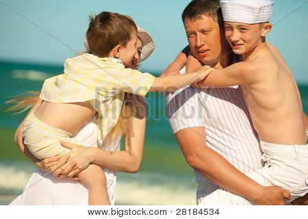 Happy family. Parents holding  sons in theirs arms on beach while on vacation