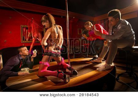 Two men shutting on mobile camera dancing woman and another one offering money to a stripper