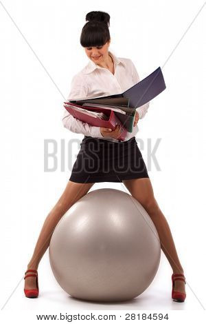 The young businesswoman simultaneously working with the documents and doing exercise with a ball