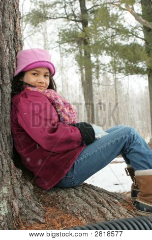Child Sitting Under Tree Outdoors In Winter