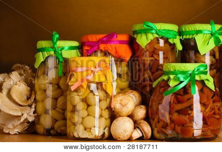delicious marinated mushrooms in the glass jars, raw champignons and oyster mushrooms on wooden shelf