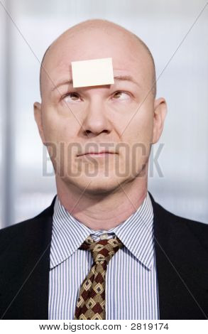 Businessman With A Blank Note On His Forehead