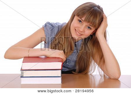 He Girl Sits At ? Table And Has Put Hands On A Pile Of Books