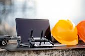 Drone, Remote Control, Laptop Computer, Smartphone And Protective Helmet At Construction Site. Using poster
