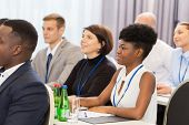 business and education concept - group of people at international conference or lecture poster