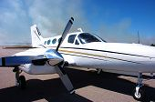 stock photo of cessna  - Cessna 421 from the side with burning grass in the background - JPG